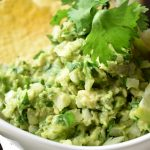 No Tomato Guacamole in a white bowl with fresh lime wedges and a golden chip in the guacamole