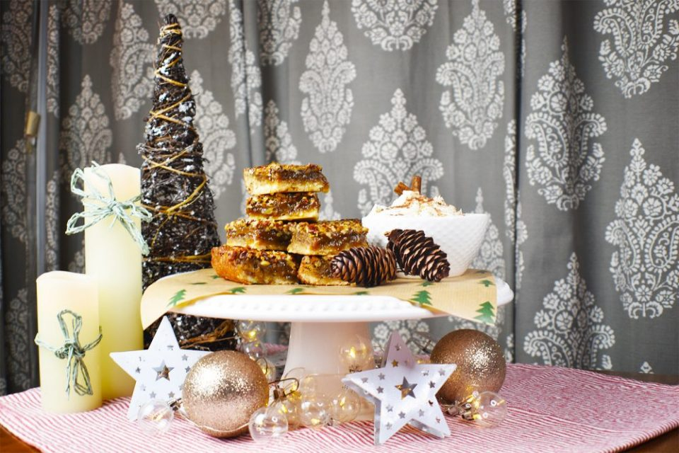 pecan pie bars on a table with decorative Christmas decorations