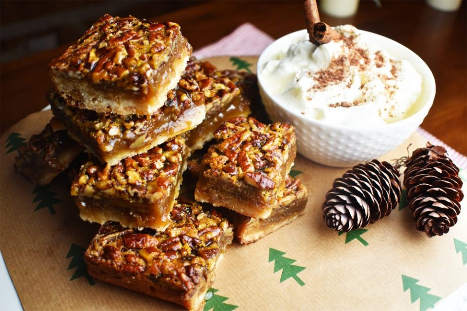 pecan pie bars on a table with Christmas tree decorated paper underneath and a small white bowl of whip cream with cinnamon sticks