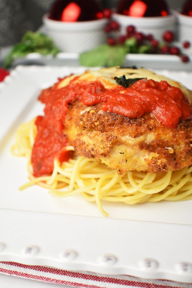 chicken parmesan on a square white plate with a Christmas decorative setting in the background
