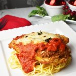 crispy chicken parmesan on a white square plate. table decorations include vibrant red cloth napkin and red decorative objects in the background