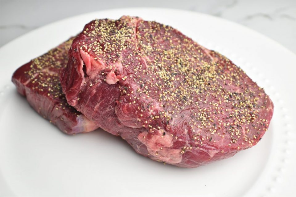 thick raw filet mignon steaks seasoned with salt and pepper on a white plate