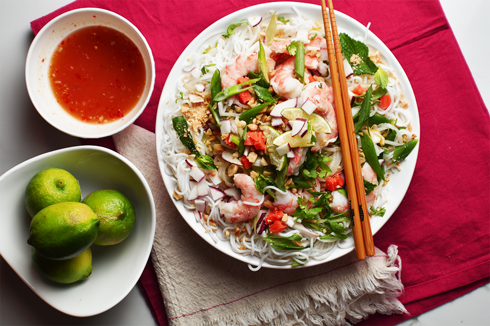 Fresh Vietnamese Vermicelli Shrimp Bowl on a red table cloth with limes in a small bowl beside main dish