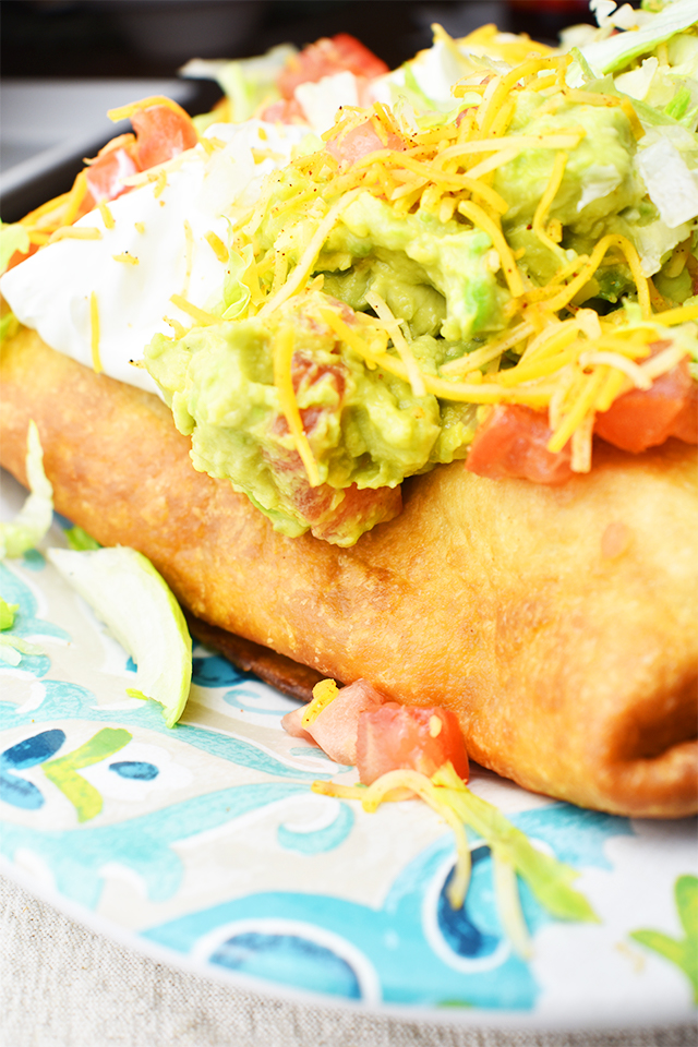 Ultimate Easy Beef Chimichangas with guacamole and sour cream on top